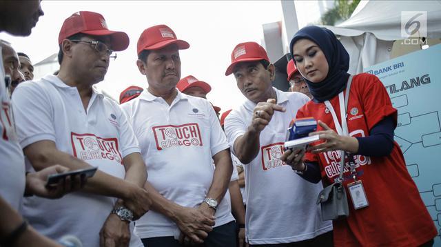 Menteri Perhubungan Budi Karya Sumadi, Menpan-RB Asman Abnur melihat simulasi pembayaran E-Tilang di Jakarta, Minggu (4/3). Layanan tersebut diharapkan dapat memudahkan masyarakat mengurus administrasi tilang. (Liputan6.com/Faizal Fanani)