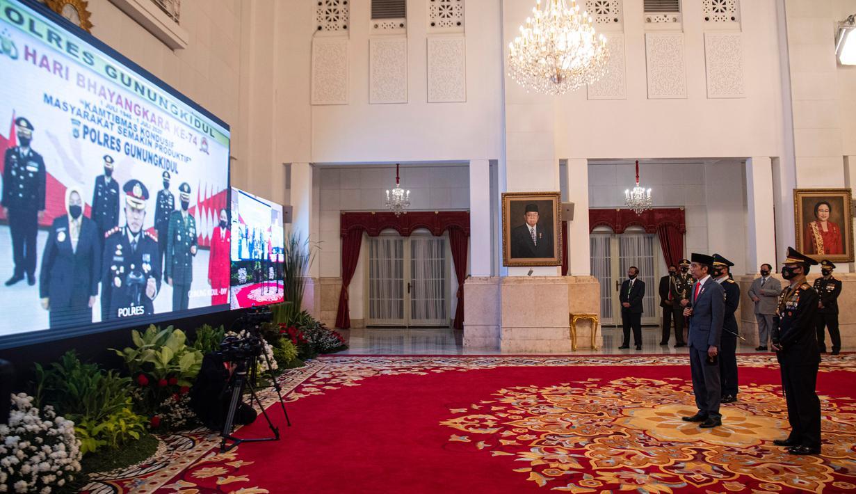 Presiden Joko Widodo (kedua kanan) didampingi Kapolri Jenderal Pol Idham Aziz (kanan) menyapa peserta upacara secara virtual dalam Peringatan Ke-74 Hari Bhayangkara Tahun 2020 di Istana Negara, Jakarta, Rabu (1/7/2020). (ANTARA FOTO/Sigid Kurniawan/POOL)