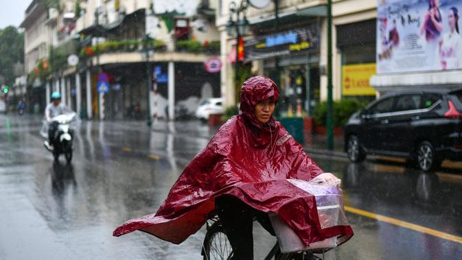 Pejalan kaki yang mengenakan jas hujan mengendarai sepeda saat hujan deras di Hanoi (14/10/2020). Badai tropis Nangka menghantam Vietnam tengah-utara yang mengakibatkan bencana alam, terutama hujan lebat dan banjir, telah menyebabkan 28 orang tewas dan 12 lainnya hilang. (AFP Photo/Manan Vatsyayana)