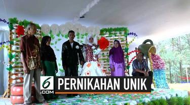 Sepasang pengantin asal Purworejo menggelar pernikahan unik. Mereka menggunakan barang-barang bekas sebagai aksesoris di pernikahannya.