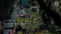 Petugas pertamanan DKI Jakarta membersihkan pohon usai dipangkas di Jalan Sutan Syahrir, Jakarta, Kamis (15/8/2019). Pemangkasan pohon tersebut dilakukan untuk menghidari pohon tumbang yang diakibatkan oleh angin dan hujan lebat saat musim penghujan tiba. (Liputan6.com/Faizal Fanani)