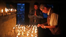 Seorang pria setengah baya menyalakan lampu minyak pada festival Kuse Aunsi di kuil Hindu Gokarneshwar di Kathmandu, Nepal (21/8). Kuse Aunsi lebih dikenal dengan sebutan Gokarna Aunsi. (Niranjan Shrestha/AP)