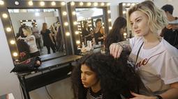 Model saat ditata rambutnya di belakang panggung sebelum tampil membawakan busana koleksi Beira selama Sao Paulo Fashion Week di Sao Paulo, Brasil (16/10/2019). SPFW ke-48 akan berlangsung hingga 18 Oktober.  (AP Photo / Nelson Antoine)