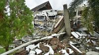 Pemandangan umum menunjukkan bangunan runtuh di Mamuju sehari setelah gempa bumi magnitudo 6,2 mengguncang Sulawesi Barat, Sabtu (16/1/2021). Petugas Badan Penanggulangan Bencana Daerah (BPBD) masih mendata jumlah kerusakan dan korban akibat gempa bumi tersebut. (Firdaus / AFP)