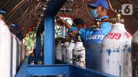 Petugas mengisi tabung oksigen di halaman gedung MUI Kota Tangerang, Banten, Kamis (15/7/2021). Kegiatan tersebut guna memudahkan warga Kota Tangerang dalam mengisi Oxygen Medis yang di masa PPKM Darurat yang kini sulit untuk mencari tempat pengisian tersebut. (Liputan6.com/Angga Yuniar)