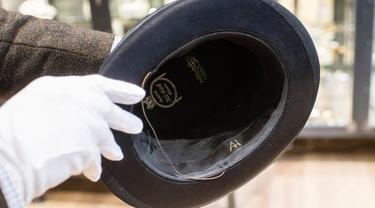 Pegawai memegang topi berinisial AH sebelum lelang memorabilia Nazi di Grasbrunn, Jerman, Rabu (20/11/2019). Menurut rumah lelang Hermann Historica dalam websitenya, topi Adolf Hitler tersebut terjual dengan harga 50 ribu euro atau sekitar Rp 781,7 juta. (Matthias Balk/dpa via AP)