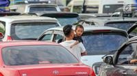 Pemudik bersama anaknya saat menanti waktu masuk kapal penyebrangan di Dermaga 1 Pelabuhan Penyebrangan Merak, Banten, Sabtu (1/6/2019). (Liputan6.com/Helmi Fithriansyah)