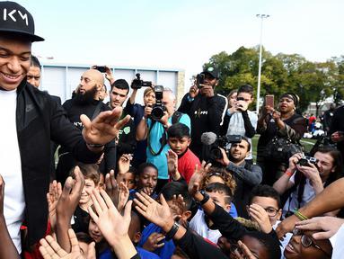 Bintang Prancis, Kylian Mbappe, menyapa anak-anak saat mengunjungi markas AS Bondy di Paris, Rabu (17/10). Kunjungan ke klub pertamanya ini dilakukan setelah dirinya meraih gelar Piala Dunia 2018. (AFP/Franck Fife)