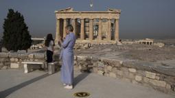 Pengunjung berdiri dekat Kuil Parthenon di Bukit Acropolis, Athena, Yunani, Senin (18/5/2020). Yunani kembali membuka kota kuno Acropolis serta situs-situs lainnya setelah dua bulan ditutup selama lockdown akibat pandemi virus corona COVID-19. (AP Photo/Petros Giannakouris)