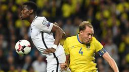 Gelandang Prancis, Paul Pogba, duel udara dengan bek Swedia, Andreas Granqvist, pada laga kualifikasi Piala Dunia 2018 di Stadion Friends Arena, Solna, Jumat (9/6/2017). Swedia menang 2-1 atas Prancis. (AFP/Franck Fife)