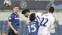 Penyerang Real Madrid, Marco Asensio mencoba melakukan sundulan ke gawang di depan gelandang Atalanta, Marten de Roon pada leg pertama babak 16 besar Liga Champions di Stadion Gewiss, Kamis (25/2/2021) dini hari WIB. Real Madrid harus susah payah kalahkan Atalanta 1-0. (AP Photo/Luca Bruno)