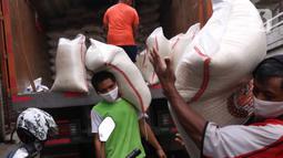 Pekerja tengah menurunkan beras yang akan di jual di Jakarta, Senin (21/12/2020). Kenaikan harga beras yang biasa terjadi saat momen akhir dan awal tahun diyakini tidak terjadi pada periode kali ini. (Liputan6.com/Angga Yuniar)