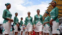 Sejumlah grid girl atau gadis pendamping berjalan sebelum dimulainya Grand Prix Formula 1 Malaysia di Sepang (1/10). Para gadis payung ini terlihat cantik dan seksi dengan busana yang dikenakannnya. (AFP Photo/Manan Vatsyayana)
