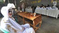 Petugas dengan kostum pocong mengawasi jalannya pemungutan suara Pemilu 2019 di TPS 073, Gunung Balong 1, Lebak Bulus, Jakarta Selatan, Rabu (17/4). TPS 073 ini mengambil tema horor, di mana para petugasnya mengenakan kostum beragam jenis hantu. (merdeka.com/Arie Basuki)