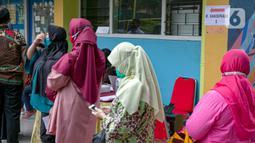 Para guru antre untuk menjalani vaksinasi COVID-19 di SMA 70, Jakarta, Rabu (25/2/2021). Sebanyak 600 orang dari profesi guru, tenaga kependidikan, dan dosen akan divaksin COVID-19 hari ini. (Liputan6.com/Faizal Fanani)