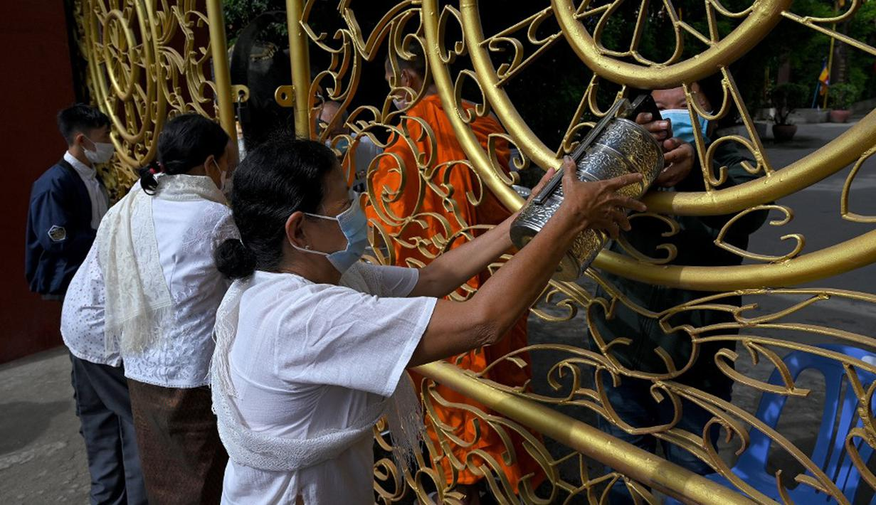 Warga memberikan makanan dan sedekah kepada biksu Buddha saat Festival Pchum Ben (Festival Kematian) di luar pagoda di Phnom Penh, Kamboja, 24 September 2021. Pihak berwenang menghentikan perayaan Festival Kematian karena pandemi COVID-19. (TANG CHHIN Sothy/AFP)