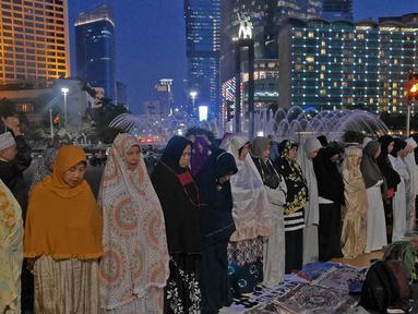 Massa Gerakan Nasional Kedaulatan Rakyat melaksanakan salat magrib di sela aksi unjuk rasa di depan kawasan Bundaran HI, Jakarta, Selasa (21/5/2019). Dalam aksinya, mereka Bawaslu memeriksa hasil Pemilu 2019 yang dinilai banyak terdaopat kecurangan. (Liputan6.com/Herman Zakharia)