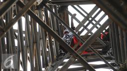Seorang pria memanjat menara sutet di kawasan Pasar Senen, Jakarta, Selasa (27/9). Pria nekat tersebut berencana memasang bendera merah putih dengan sebuah kalimat berisi permintaan untuk menghukum oknum Dandim. (Liputan6.com/Gempur M Surya)