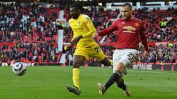 Bek Manchester United (MU), Luke Shaw mengoper bola di depan gelandang Fulham, Andre-Frank Zambo Anguissa (tengah) pada pekan 37 Liga Inggris di Stadion Old Trafford, Rabu (19/5/2021) dinihari WIB. MU kembali gagal menang setelah ditahan imbang 1-1 oleh tamunya Fulham. (Paul ELLIS/POOL/AFP)