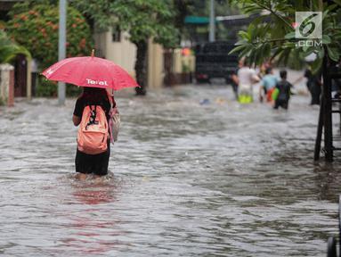 Seorang warga melintasi banjir di jalan Pd. Karya, Jakarta, Kamis (13/12). Hujan yang mengguyur Jakarta Sore tadi menyebabkan banjir setinggi 40cm  menggenangi kawasan Jalan Pd. Karya dan Jalan Bangka. (Liputan6.com/Faizal Fanani)
