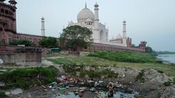 Pemandangan Taj Mahal dari seberang parit di tepi sungai Yamuna, Agra, India, Jumat (4/5). Kini, warna Taj Mahal  yang seharusnya putih marmer berubah menjadi kuning bahkan cokelat dan hijau di sejumlah sisinya. (AFP/CHANDAN KHANNA)