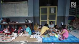 Warga beristirahat di Gedung SMP Negeri 26, Jalan Kebon Pala, Kampung Melayu, Jatinegara, Jakarta Timur, Selasa (6/2). Sebanyak 42 KK mengungsi di tempat tersebut akibat rumahnya terendam banjir. (Liputan6.com/Arya Manggala)