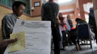 Salah seorang ibu menunjukkan nomor antrean pengambilan token PPDB di SMPN 92, Jakarta, Senin (25/6). Meski dibuka pada pada pukul 08.00 WIB, para orang tua calon siswa baru sudah mendatangi sekolah sejak pukul 6 pagi. (Merdeka.com/Iqbal S Nugroho)