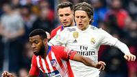 Gelandang Real Madrid, Luka Modric berusaha merebut bola yang dibawa gelandang Atletico Madrid, Thomas Lemar selama pertandingan lanjutan La Liga Spanyol di stadion Wanda Metropolitano (9/2). Real Madrid menang 3-1. (AFP Photo/Gabriel Bouys)