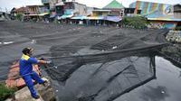 Petugas melepas kain waring atau jaring yang menutupi Kali Item di Kemayoran Jakarta, Rabu (14/11). Pelepasan waring yang sebagian dalam kondisi sudah robek itu dilakukan lantaran banyak warga yang membuang sampah di atasnya (Merdeka.com/Iqbal S. Nugroho)