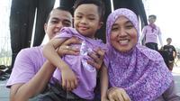 Raga (tengah) diapit kedua orangtuanya usai acara World Down Syndrome Day di Lapangan Monas Jakarta, Minggu pagi (22/3/2015).
