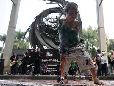 """Sadikin Pard (53) membuat karya lukisan dengan kedua kakinya saat Indonesian Art Festival """"Pesta Seni Rupa Indonesia"""" di Museum Nasional, Jakarta, Minggu (10/11/2019). Keterbatasan seniman asal Malang tersebut tidak melemahkan niatnya dalam dunia berkesenian. (merdeka.com/Iqbal S. Nugroho)"""