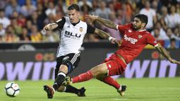 Striker Valencia, Santi Mina, berebut bola dengan gelandang Sevilla, Ever Banega, pada laga La Liga Spanyol di Stadion Mestalla, Sabtu (21/10/2017). Valencia menang 4-0 atas Sevilla. (AFP/Jose Jordan)