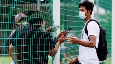Kiper Timnas Indonesia, Muhammad Riyandi, melakukan wawancara dari balik jaring usai latihan di Lapangan D, Senayan, Jakarta. (Bola.com/ M Iqbal Ichsan)