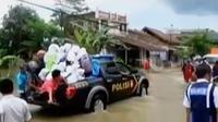 Untuk membantu masyarakat yang akan menyeberang, polisi menggunakan mobil patroli.