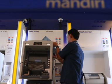 Teknisi memperbaiki mesin ATM di Jakarta, Selasa (27/9). Pemerintah mewajibkan seluruh perbankan di Indonesia untuk mengonversikan kartu ATM dari teknologi magnetic stripe  menjadi teknologi cip yang diyakini lebih aman. (Liputan6.com/Angga Yuniar)