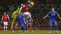 Kiper Chelsea Petr Cech duel udara dengan gelandang Arsenal Mesut Ozil pada pertandingan sepak bola Liga Inggris antara Arsenal vs Chelsea di Stadion Emirates, London (24/12/13). (AFP/Adrian Dennis)