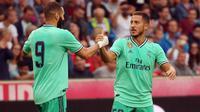 Selebrasi Eden Hazard bersama Karim Benzema setelah menjebol gawang Real Bull Salzburg dalam laga persahabatan di Austria (7/8/2019). (APA/AFP/Krugfoto)