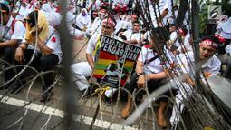 Massa dari Komite Nusantara Aparatur Sipil Negara (KNASN) menggelar aksi damai di depan Istana Negara, Jakarta, Rabu (19/7). Mereka mendesak pemerintah merevisi UU No 5 Tahun 2014 tentang Aparatur Sipil Negara (ASN). (Liputan6.com/Faizal Fanani)