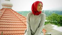 Perempuan yang satu ini juga terlihat piawai dalam pemilihan warna. Seperti ini contohnya, Tika mengenakan hijab berwarna merah dengan paduan busana berwarna abu-abu. (Instagram/tika_ramlan)