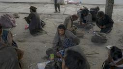 Para pecandu narkoba duduk di pinggir jalan saat mereka mengonsumsi narkoba di Kabul,  Afghanistan, 21 September 2021. Afghanistan dikenal sebagai penghasil opium nomor satu di dunia. (BULENT KILIC/AFP)