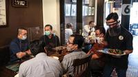 Pramusaji menggunakan pelindung wajah, masker dan sarung tangan saat melayani pelanggan di The Atjeh Connection Coffee and Resto, Jakarta, Senin (8/6/2020). Tempat ini siap menerapkan protokol kesehatan dalam menerapkan tatanan kehidupan baru atau 'new normal'. (Liputan6.com/Faizal Fanani)