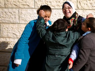 """Seorang guru dengan Down Syndrome yang bernama Hiba Al-Sharfa bermain dengan muridnya di sekolah Asosiasi Hak Hidup di Kota Gaza (21/12). Hiba adalah seorang guru yang memeliki """"kebutuhan khusus"""" di Jalur Gaza. (Reuters/Suhaib Salem)"""