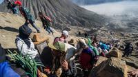 Warga Tengger mendaki Gunung Bromo membawa persembahan hasil bumi selama Festival Yadnya Kasada di Probolinggo, Jawa Timur (10/7). Warga Tengger melakukan ritual lempar hasil bumi sebagai wujud syukur pada Sang Hyang Widi. (AFP Photo/Juni Kriswanto)
