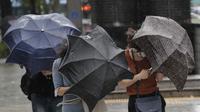 Orang-orang berjuang dengan payung mereka melawan angin kencang dan hujan di pusat kota Seoul, Korea Selatan, Kamisn (3/9/2020). Topan Maysak kuat melanda wilayah semenanjung Korea. (AP Photo/Lee Jin-man)