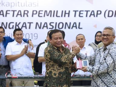 Ketua KPU RI, Arief Budiman (kanan) bersalaman dengan Ketua Bawaslu RI, Abhan saat menyerahkan soft copy DPT tingkat nasional di Jakarta, Rabu (5/9). Sebelumnya, KPU menggelar rapat pleno rekapitulasi DPT nasional. (Liputan6.com/Helmi Fithriansyah)