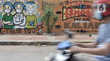 Pengendara melintas di depan mural dukungan untuk tim medis Covid-19 di kawasan Sunter, Jakarta, Rabu (27/5/2020). Mural bergambarkan sosok tim medis dan ungkapan doa ini berada di seberang RS Darurat Wisma Atlet yang dibuat oleh Karang Taruna Kelurahan Sunter Jaya. (merdeka.com/Iqbal S. Nugroho)