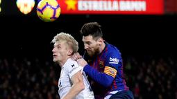 Pemain Barcelona, Lionel Messi (kanan) berebut bola udara dengan pemain Valencia Carlos Soler saat bertanding dalam lanjutan Liga Spanyol di Camp Nou, Spanyol, Minggu (3/2). Dua gol Messi membuat pertandingan berakhir 2-2. (AP Photo/Manu Fernandez)