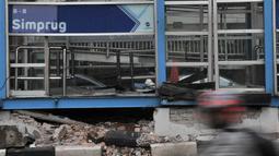 Kendaraan melintas di depan Halte Transjakarta Simprug usai tertabrak truk kontainer, Jakarta, Kamis (19/4). Kaca jendela halte pecah serta plafon dan lantai jebol. (Merdeka.com/Iqbal Nugroho)