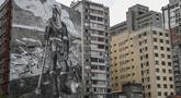 "Mural berjudul ""The Forest Brigadir"" menggunakan abu kebakaran hutan Amazon oleh seniman Thiago Mundano, menutupi kompleks apartemen di Sao Paulo, Brasil, Jumat (15/10/2021). Mural bergambar petugas damkar yang berdiri di tengah peristiwa deforestasi, kebakaran, dan hewan mati. (AP/Marcelo Chello)"