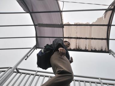 Pejalan kaki melintasi jembatan penyeberangan orang (JPO) di Jalan Yos Sudarso, Jakarta, Kamis (8/11). JPO mengalami kerusakan pada bagian atap yang jebol. (Merdeka.com/Iqbal Nugroho)